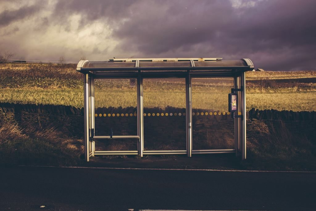 Gray and black waiting shed under cloudy sky.